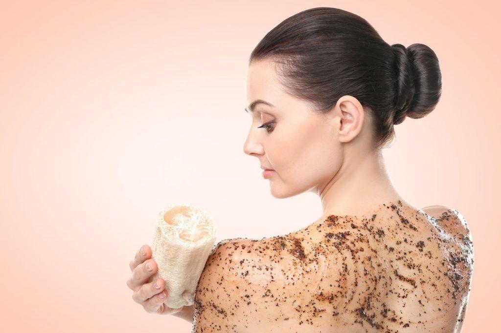 Cilt temizliği için peeling uygulayan ve ölü derilerini temizleyen arkası dönük kadın