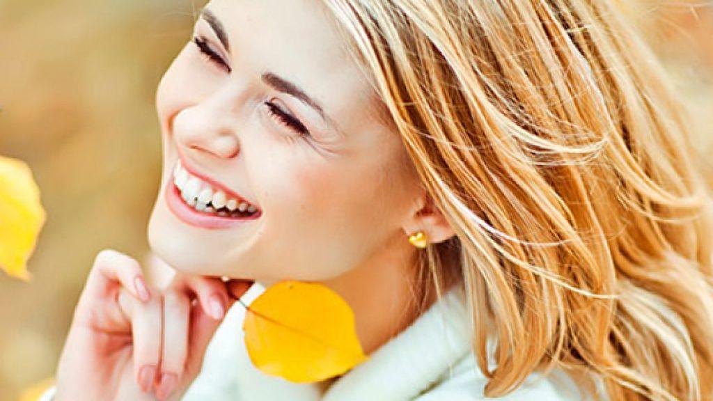parlak bir cilt sahibi olan gülümseyen bir kadın ve sarı yapraklar